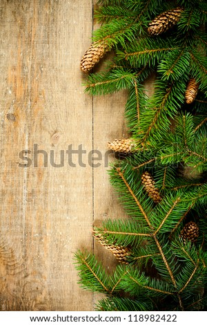 christmas fir tree with pinecones frame on a wooden board - stock photo