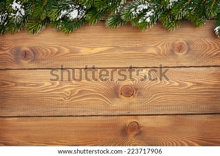 Christmas fir tree with snow on rustic wooden board with copy space - stock photo