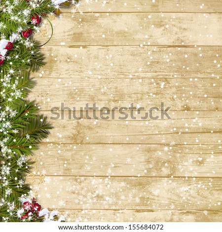 Christmas fir tree with snowfall  on a wooden board - stock photo