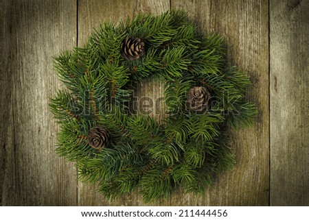 Christmas fir wreath on vintage wooden background, horizontal close-up - stock photo