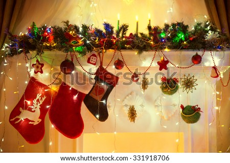 Christmas Fireplace, Family Hanging Three Socks, Xmas Lights Decoration, Tree Branches - stock photo