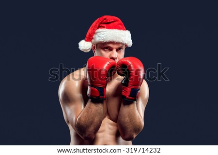 Christmas fitness boxer wearing santa hat and red gloves boxing on black background - stock photo