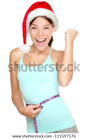 Christmas fitness woman excited about weight loss measuring waist with measuring tape wearing santa hat screaming excited. Mixed race fitness model isolated on white.