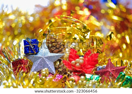 Christmas flower,five-pointed star,pine cone with box in the golden tinsel defocused backgrounds - stock photo