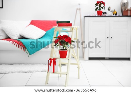 Christmas flower poinsettia and decorations on decorative ladder with Christmas decorations, on light background - stock photo