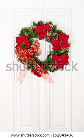 Christmas flower wreath hanging on white wood door - stock photo