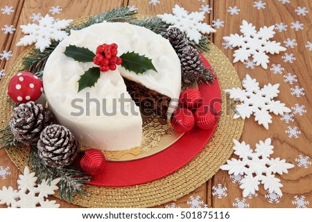 Christmas food still life with iced fruit cake, holly, snow covered winter greenery, fly agaric decorative mushroom  and white snowflake and red bauble decorations over oak background.