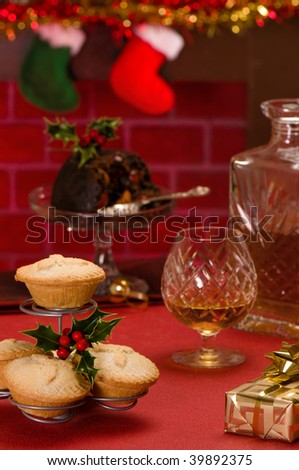 Christmas food with glass and decanter of brandy and gift with fireplace in background - stock photo
