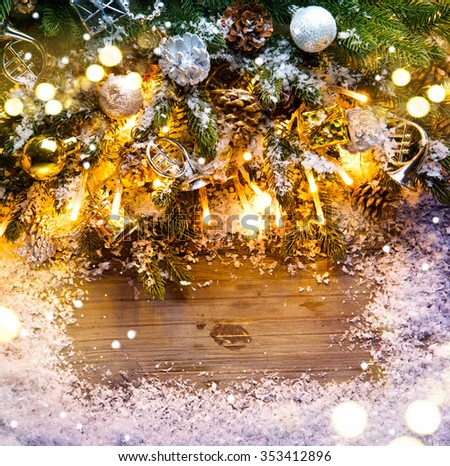 Christmas frame design. Fir tree with vintage decoration on dark wooden board background with snow. Border art design with Christmas tree, baubles and light garland - stock photo
