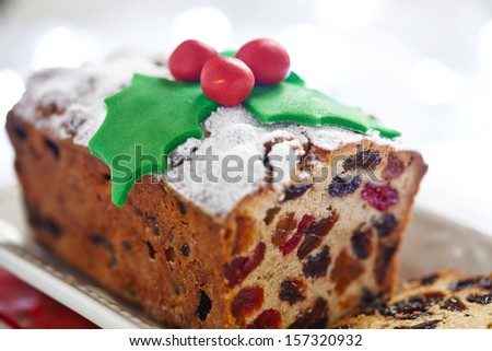 Christmas fruit cake decorated with holly and berries - stock photo
