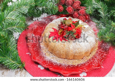 Christmas Fruit Cake. Homemade Christmas fruit cake full of cherries, raisins, currants, walnuts  and other candied fruit (decorated with an edible poinsettia) - stock photo