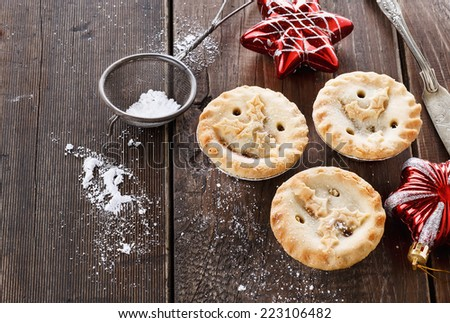 Christmas fruit mince pies and red Christmas ornaments over rustic wooden background - stock photo
