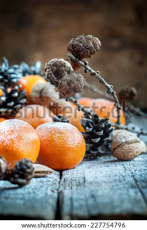Christmas Fruits. Tangerines, Pine cones, Walnuts, Almonds and Candles on Wooden Background, holiday decor - stock photo