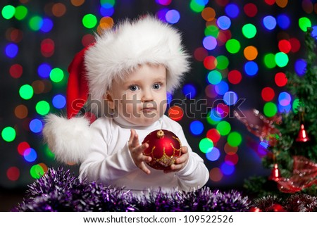 christmas funny baby in Santa Claus hat on bright festive background - stock photo