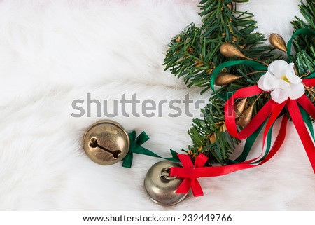 Christmas garland and small bells on white fur - stock photo