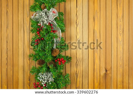 Christmas garland from pine tree on wooden background.