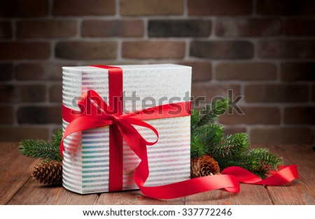Christmas gift box and fir tree branch on wooden table - stock photo