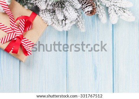 Christmas gift box and fir tree branch on wooden table. Top view with copy space - stock photo
