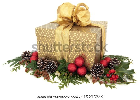 Christmas gift box in gold with bow, with red bauble cluster, holly, ivy, mistletoe, pine cones and winter greenery over white background. - stock photo
