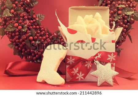 Christmas gift box of shortbread biscuit cookies with festive ornament decorations left out for Santa with retro vintage filter. - stock photo