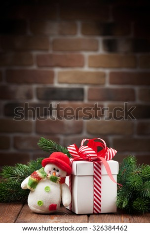 Christmas gift box, snowman toy and fir tree branch on wooden table. View with copy space - stock photo