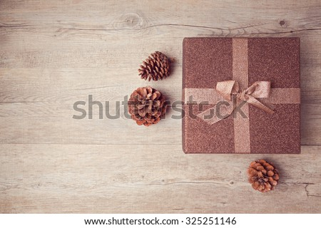 Christmas gift box with pine corn on wooden background. View from above - stock photo