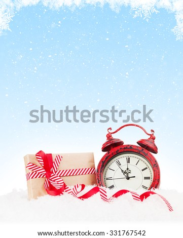 Christmas gift boxe and alarm clock in snow with copy space - stock photo