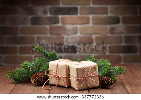 Christmas gift boxes and fir tree branch on wooden table. View with copy space - stock photo