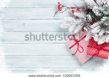 Christmas gift boxes and fir tree on wooden background. Top view with copy space