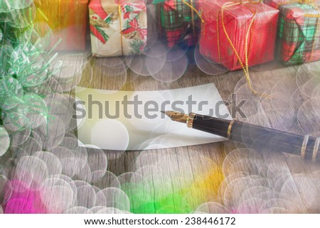 Christmas gift boxes and fountain pen over wooden background
