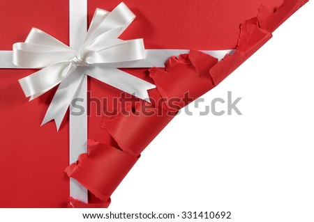 Christmas gift corner torn open, white ribbon bow, red paper background, copy space - stock photo