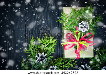 Christmas gift in decorated box at dark wooden table. Top view, copy space. - stock photo