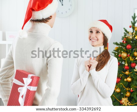 Christmas gift. man gives a woman a surprise gift present box  - stock photo