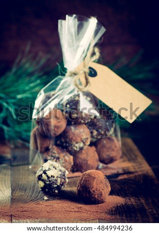 Christmas gift of chocolate truffles on dark wooden background vintage toned