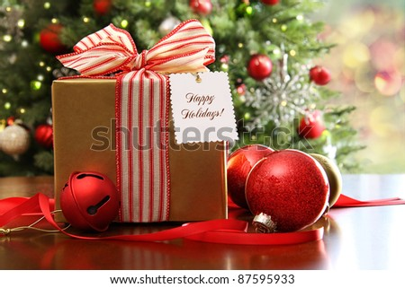 Christmas gift sitting on a table with a tree in the background - stock photo