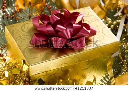 Christmas gift surrounded by golden tinsel