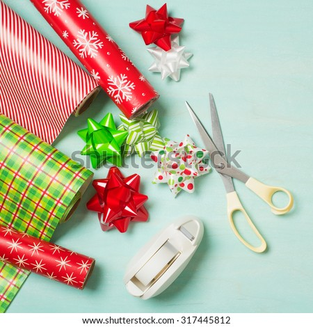 Christmas Gift Wrapping Party Time with Colorful Paper, Ribbon Bows, Scissors and Tape on Cyan Blue Shabby Chic Wood Board Background with Square Crop and Room or Space for copy, text, your words.   - stock photo