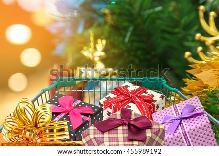 Christmas gifts and presents in shopping trolley with christmas decorations and blurred lights on christmas tree background.  - stock photo