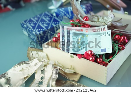 Christmas gifts and toys with euro banknotes in a center of composition, shot with selective focus - stock photo