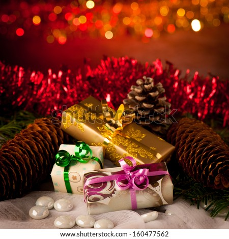 Christmas gifts arranged on a table with spruce branches and lights - stock photo