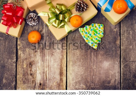 Christmas gifts boxes on the old dark boards. Christmas background. Christmas decorations. New Year background. Xmax background. Selective focus on a bow-knot. Small depth of field. Toned image. - stock photo