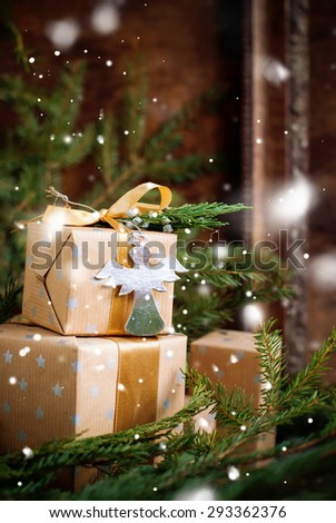 Christmas Gifts Decorated with Cardboard Angel, Ribbon and Natural Cypress  on Holiday Vintage Background in front of coniferous branch. Snow effect