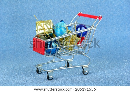 Christmas gifts in shopping trolley, on blue shiny background - stock photo