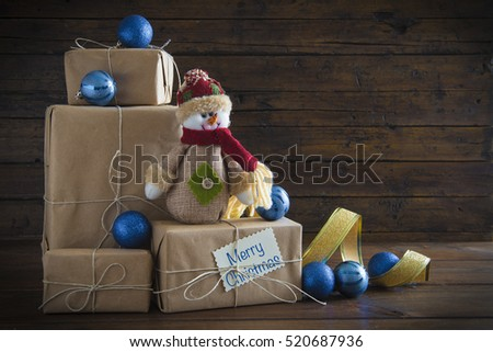 Christmas gifts on a wooden background with ornaments and a copy space
