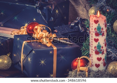 Christmas gifts with a Xmas candle and shiny baubles - stock photo