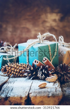 Christmas Gifts with Linen Cord, Cinnamon, Pine cones, Nuts on Wooden Background. Toned image - stock photo