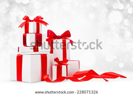 Christmas gifts with red ribbons on light background