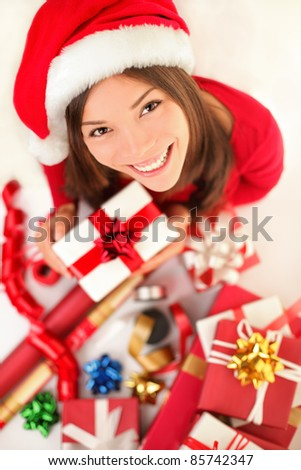 Christmas gifts. Woman wrapping christmas presents wearing santa hat. Christmas preparations concept with beautiful smiling happy content young woman in her twenties. - stock photo