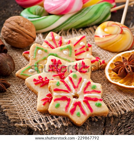 Christmas gingerbread cookies and lollipops on old wooden background - stock photo
