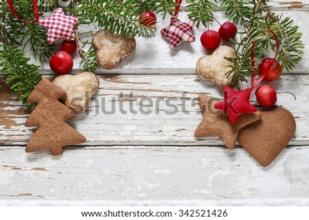 Christmas gingerbread cookies, fir branches and paradise apples on a white wooden background - stock photo